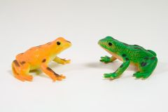 Toy Frogs Face Off. A green and orange plastic frogs royalty free stock photography