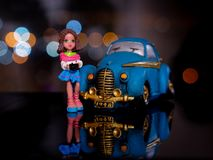 Toy girl standing at the blue car at night. royalty free stock photography