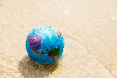 Mini globe close-up on the sand. Toy globe shot close-up lies on the sandy beach of Koh Samui Stock Photo