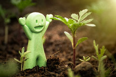 Toy Green Baby Doll happy with seedlings. Royalty Free Stock Image