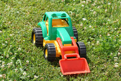 Toy green tractor on the grass. Royalty Free Stock Image