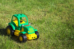 Toy green-yellow tractor on the grass. Stock Photography