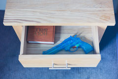 Toy gun and bible in drawer Royalty Free Stock Photography