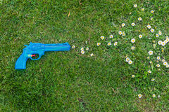 Toy gun on grass shooting daisies. A blue toy gun placed on a lawn in a position that makes it look as if it's shooting daisies Royalty Free Stock Images