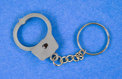 Toy handcuffs keychain on blue background Stock Photo