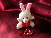 Toy hare and two wedding rings on a red cloth.  Royalty Free Stock Image