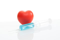Toy heart and syringe with blue solution inside - studio shot Royalty Free Stock Photo