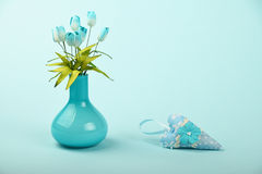Toy heart and vase with silk tulips on blue background Royalty Free Stock Image