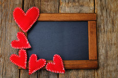 Toy hearts on a frame with a chalkboard Stock Images