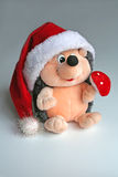 A toy hedgehog decorated for Christmas. Fluffy toy Royalty Free Stock Photo