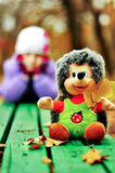 Toy hedgehog sitting on a bench on the background of the girl Royalty Free Stock Photo