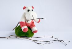 Toy hippopotamus handmade, sits on a moss, holds a branch in its hands. Concept Hahdmade Royalty Free Stock Photos