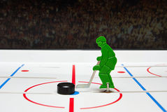 Toy hockey player and puck. In a center of stadium Royalty Free Stock Photography