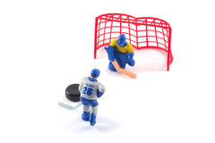 Toy hockey players playing hockey. Ice hockey player trying to score a goal against the enemy Stock Photos