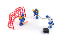 Toy hockey players playing hockey. Ice hockey player trying to score a goal against the enemy Stock Photography