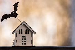 Toy house with a bat, Background for halloween. Autumn, loneliness, threat Royalty Free Stock Images