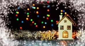 Toy house with candles on a dark background. With white snow and decorations numbers 2018 for a new year christmas Stock Images