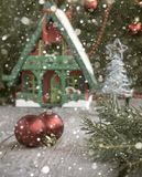 Toy house with Christmas decoration in front. Christmas background and decorations. Soft focus Royalty Free Stock Photo
