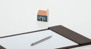 Toy house, clipboard with empty sheet of paper and a pen on the Stock Photos