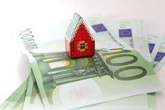 Toy house and coins Stock Photography