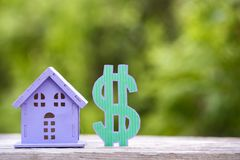 Toy house with a dollar symbol on a summer green background. Royalty Free Stock Photography
