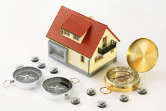 Toy house and eleven different compasses Stock Photography