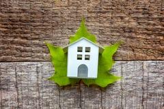 Toy House en groen esdoornblad op houten achtergrond Royalty-vrije Stock Fotografie
