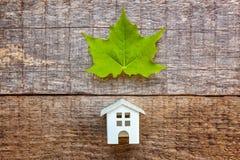 Toy House en groen esdoornblad op houten achtergrond Stock Afbeeldingen