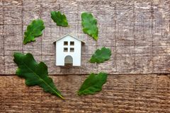 Toy House en groene eiken bladeren op houten achtergrond Royalty-vrije Stock Afbeeldingen