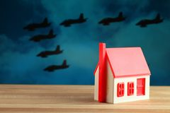 Toy house and formidable silhouettes of military aircraft Royalty Free Stock Images