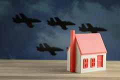 Toy house and formidable silhouettes of military aircraft Royalty Free Stock Photo