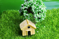 Toy house on the grass with a tree. Royalty Free Stock Photography