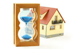 Toy house and hourglass with blue sand Royalty Free Stock Photography