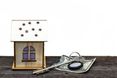 Toy house with keys and cash on old wooden Board, on white isolated background royalty free stock images