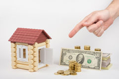 Toy house, lie near money to buy, hand on top shows a finger Stock Photo