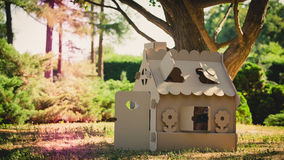 Toy house made of corrugated cardboard in the city park. On the grass. The concept of eco-estate Stock Image