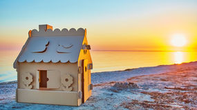 Toy house made of corrugated cardboard in the sea Royalty Free Stock Photography