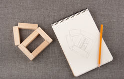 Toy house made of wooden blocks, notepad and pencilon grey backg Royalty Free Stock Photo