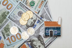 Toy house on many dollar banknotes and euro coins Stock Photo