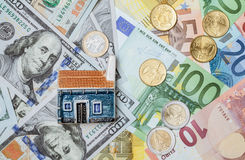 Toy house on many euro and dollar banknotes and euro coins Royalty Free Stock Images
