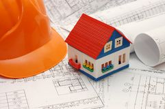 Toy house model on blueprints with helmet near by Royalty Free Stock Images