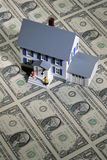 Toy house on money. Toy house with figures on a sheet of one dollar bills stock photos