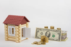 Toy house near money is to purchase a pack of bills and a stack of coins Royalty Free Stock Image