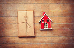 Toy house and package on wooden background. Stock Photos
