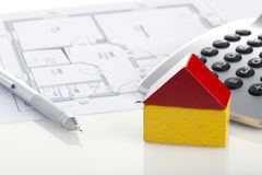Toy house, pencil and calculator on floor plan Stock Photography