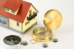 Toy house and seven different compasses isolated Stock Photography