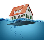 Toy house sinking underwater on a white background concept Stock Image