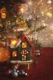 A toy house stands under a hood next to a decorated Christmas tree Royalty Free Stock Images