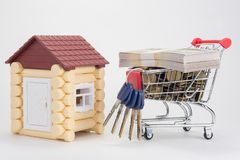 Toy house, trolley with money and a bunch of house keys royalty free stock photo