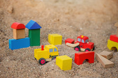 Toy house and trucks made of wooden blocks in sandbox Stock Image